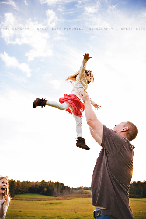 dad throwing daughter up in the air