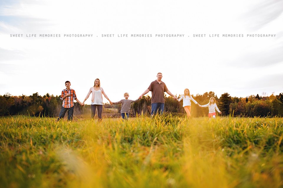 family holding hands in a field