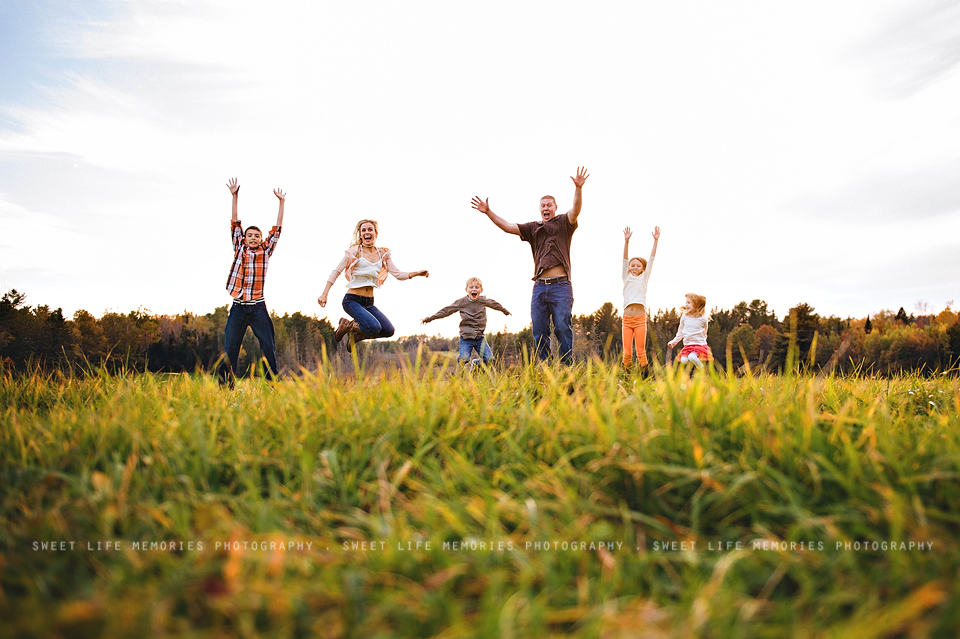 family jumping in the field