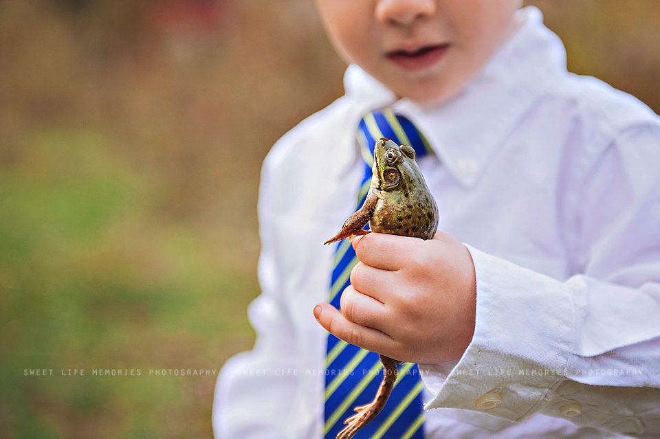 dressed up boy squeezing the frog he caught