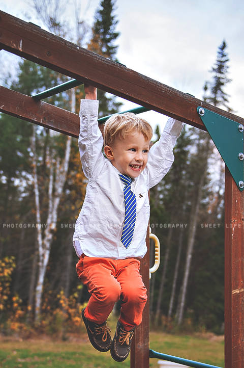 dressed up little boy hanging from monkey bars