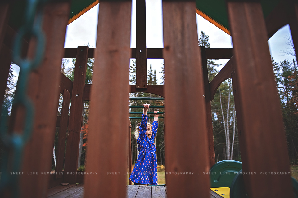 girl in blue dress hanging from monkey bars
