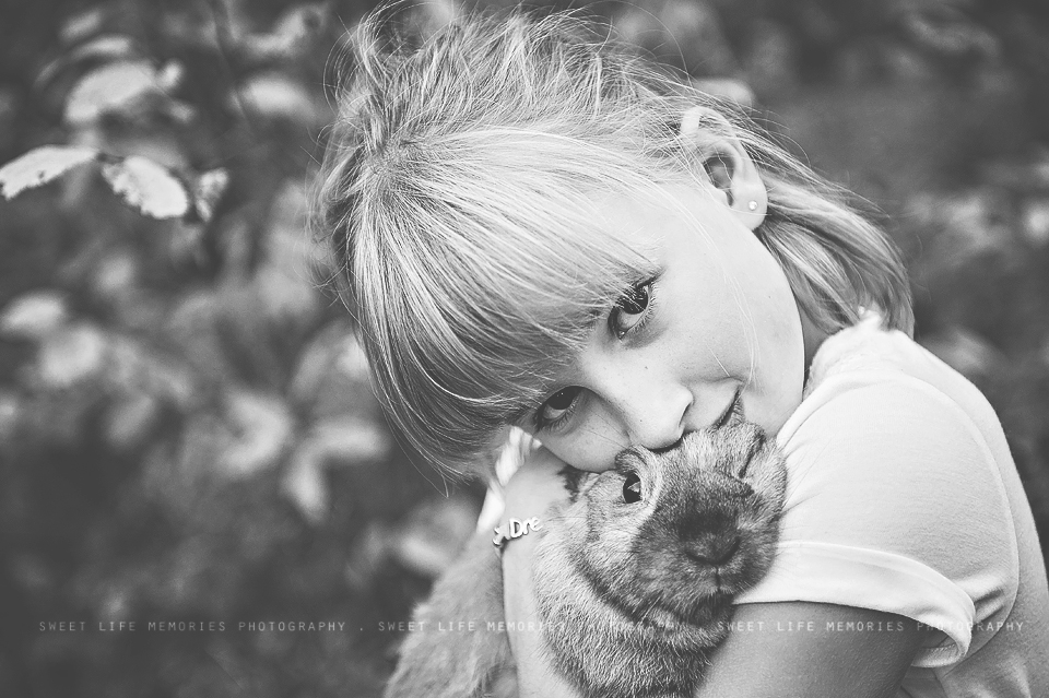 black and white photo of a little girl snuggling her bunny rabbit
