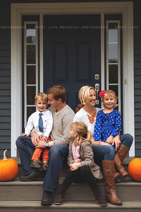 candid family portrait on the front steps flanked by pumpkins