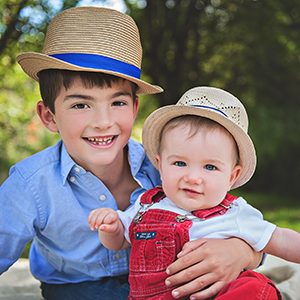 Family pictures of two cute brothers wearing red, white and blue with straw hats on.