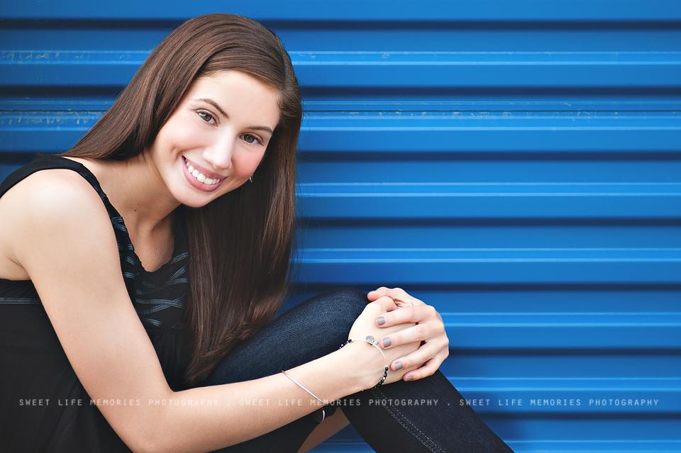 senior girl sitting on blue industrial background