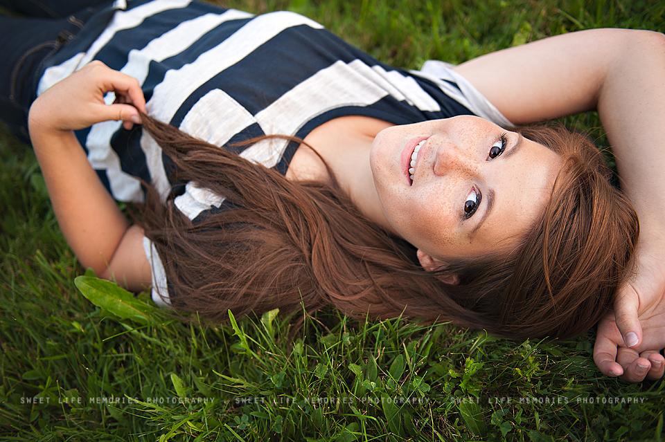 senior girl laying in grass