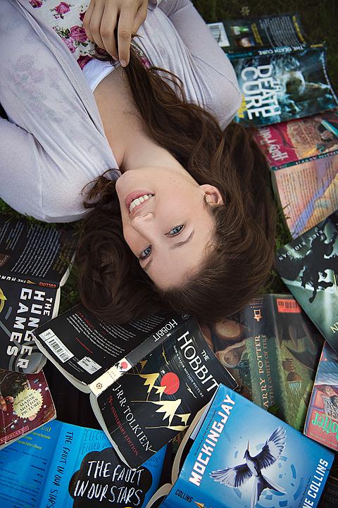 senior girl laying in books