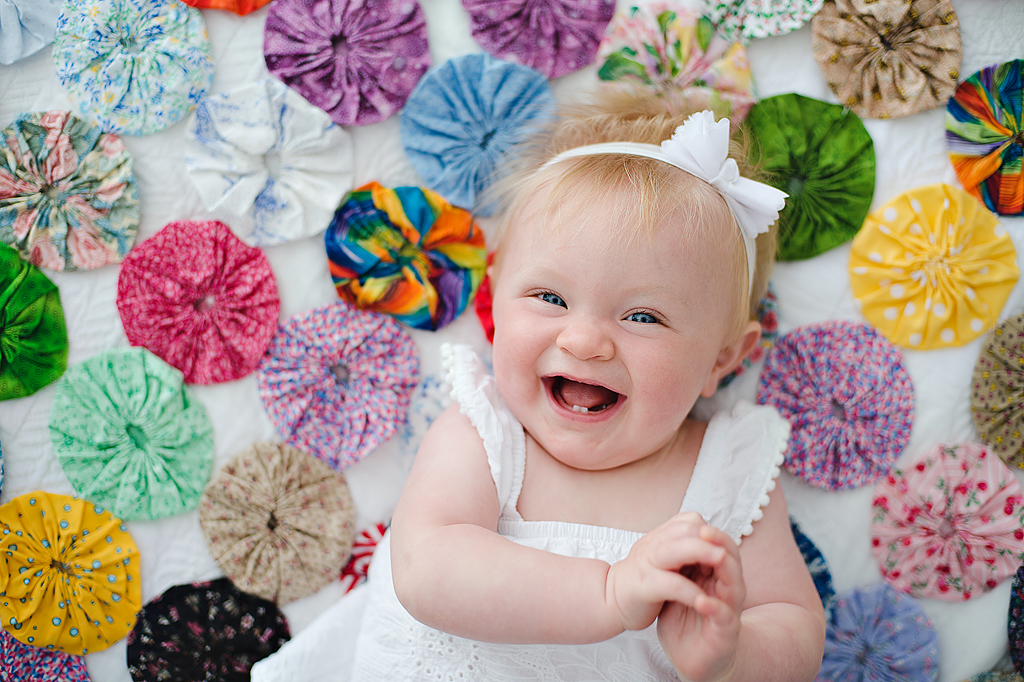 baby laughing on quilt